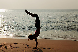 Jul. 25, 2012 - Woman practicing yoga on a beach at sunset (Credit Image: © Image Source/ZUMAPRESS.com)