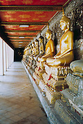 The row of Buddhas in Wat Suthat Buddhist temple, Bangkok Thailand