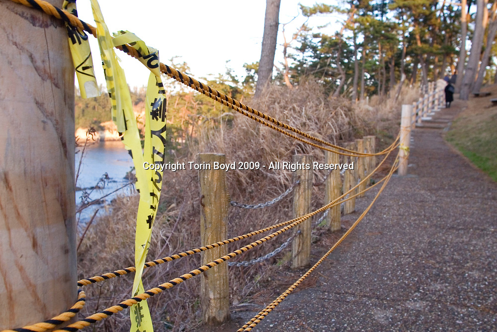 Nov. 26, 2009, Sakai City, Japan: Fence with police tape near the spot where many suicides occur at the rocky cliffs of Tojinbo, a popular tourist attraction on the Japan Sea coast that's also known for the number of suicide deaths that occur here. Located in Sakai City, Fukui Prefecture, this scenic area known for it's coastal beauty, seafood and onsen hot springs resorts now adds suicide as a reason to come here. In 2008 twenty suicides occurred here, but this figure varies between Sakai City officials and a suicide help group dedicated to preventing suicides here. Called Kokoro ni Hibiku Bunshu Henshukyoku, this NPO founded in 2004 by retired policeman Yukio Shige, who along with a group of volunteers patrols the cliffs on a daily basis to deter those contemplating jumping to their deaths. According to Shige, age 65, in the past five years since he founded his NPO, he is responsible for talking 222 people out of killing themselves. But even with Shige's efforts, the deaths here continue and as of late November, 2009, the current number of annual suicides at Tojinbo stands at thirteen. Japan has one of the highest suicide rates in the world and 2009 may surpass the record 34,427 deaths that occurred here in 2003. This increase is though to be a result of the Japanese recession which has been worsened by the global economic downturn. Depression is the number one cause for suicide in Japan, followed by illness and debt. Photo by Torin Boyd.