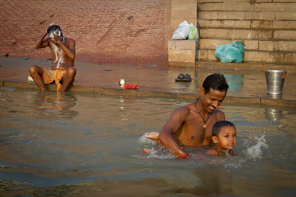 A father gives his son a swimming lesson as they bathe together in the holy Ganges River. Varanasi, India