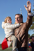 U.S. Senator and GOP presidential candidate Ted Cruz holding his youngest daughter Catherine, waves to supporters during a campaign event at Ottawa Farms December 19, 2015 in Bloomingdale, Georgia.