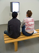two people looking at a television which is placed sideways