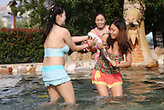 ZHENGZHOU, CHINA - SEPTEMBER 20: (CHINA OUT) <br /> <br /> Bikini Girls Compete Catching Fish <br /> <br /> Girls wearing bikinis carry a fish in the hot spring during a compete on September 20, 2015 in Zhengzhou, Henan Province of China. People who caught and held the fish for 60 seconds could take the fish away during a compete in the hot spring in Zhengzhou on Sep 20. <br /> ©Exclusivepix Media