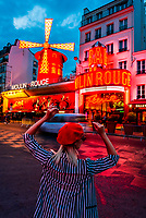 A Parisian woman in front of the Moulin Rouge (French for Red Windmill) at twilight. It is a tourist attraction in Pigalle on Boulevard de Clichy, 18th arrondissement. It is best known as the birthplace of the modern form of the can-can dance. Paris, France.