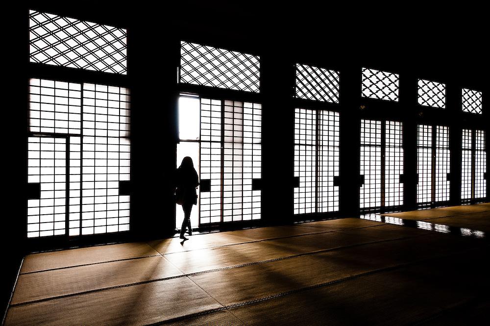A woman walks through doors covered with shoji paper at Higashi Hongang-ji Temple in Kyoto, Japan.