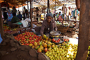 A lady selling fresh tomatoes and mangoes in a local market in Finote Selam, Ethiopia.