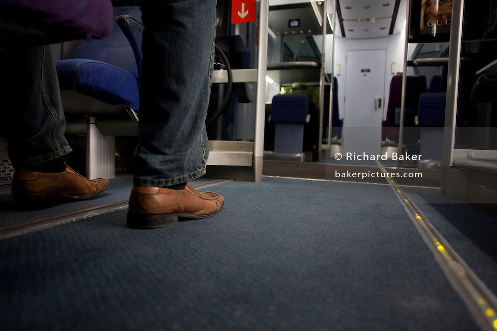 A passenger's leg is seen on the floor of a Heathrow Express train between terminals at Heathrow Airport. .