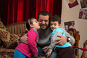 CAIRO, EGYPT - FEBRUARY 25: Al Jazeera English (AJE) producer Baher Mohamed (c) embraces his children, Fairouz (l) and Hazem,  February 25, 2015 at his family apartment in the Sheikh Zayed district on the outskirts of Cairo, Egypt. Baher, and fellow Al Jazeera defendent Mohamed Fahmy were conditionally released on Feb 12, 2015 following Egypt's highest appeal courts decision to grant them a retrial, which has since been postponed until March 8. (Photo by Scott Nelson, for the Washington Post)