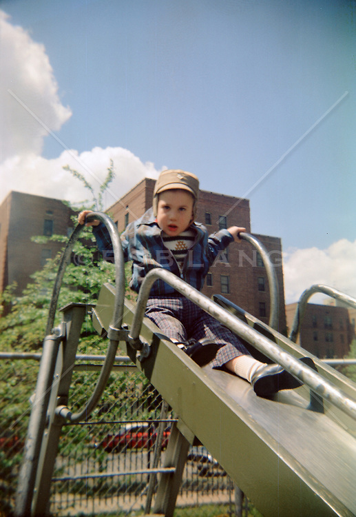 toddler on a slide in a city park, 1960's