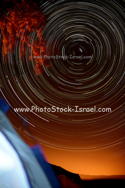 Time-exposure of polar star trails. The Pole Star, Polaris, is the short bright trail just off centre. The circular formation of the star trails is a result of the Earth's revolution in relation to the fixed stars. The different colours of the star trails results from the different intrinsic colours of the stars themselves, ranging from blue-white, through white and yellow, to orange. The photograph was taken at HaMakhtesh HaGadol (The Big Crater) Negev desert, Israel.