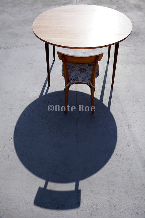 round table outside on a sunny day with one chair