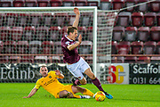 Scott Robinson (#17) of Livingston FC tackles Christophe Berra (#6) of Heart of Midlothian FC during the Ladbrokes Scottish Premiership match between Heart of Midlothian FC and Livingston FC at Tynecastle Park, Edinburgh, Scotland on 4 December 2019.