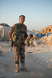 © Licensed to London News Pictures. 02/09/2015. Bashiqa, Iraq. A Kurdish peshmerga officer stands in the early morning sunlight at a defensive position located on the top of Bashiqa Mountain, Iraq.<br /> <br /> Bashiqa Mountain, towering over the town of the same name, is now a heavily fortified front line. Kurdish peshmerga, having withdrawn to the mountain after the August 2014 ISIS offensive, now watch over Islamic State held territory from their sandbagged high-ground positions. Regular exchanges of fire take place between the Kurds and the Islamic militants with the occupied Iraqi city of Mosul forming the backdrop.<br /> <br /> The town of Bashiqa, a formerly mixed town that had a population of Yazidi, Kurd, Arab and Shabak, now lies empty apart from insurgents. Along with several other urban sprawls the town forms one of the gateways to Iraq's second largest city that will need to be dealt with should the Kurds be called to advance on Mosul. Photo credit: Matt Cetti-Roberts/LNP