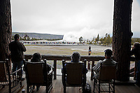 Tourists Seated on Old Faithful Lodge Patio Deck Viewing Old Faithful Geyser Eruption, Yellowstone National Park, Wyoming