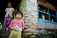 Young Sherpa girls standing outside their house, Annapurna Sanctuary, Nepal