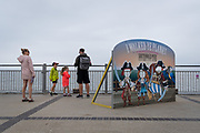 A young family stand next to a seaside cut-out board on Southwold Pier, on 14th August 2020, in Southwold, Norfolk, England.