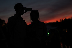 Image ©Licensed to i-Images Picture Agency. 17/07/2014. Henham Park, Suffolk, United Kingdom. A couple watch a boiling orange sunset as the hottest day of the year so far draws to an end during the Latitude Festival of music and arts . Picture by Joel Goodman / i-Images