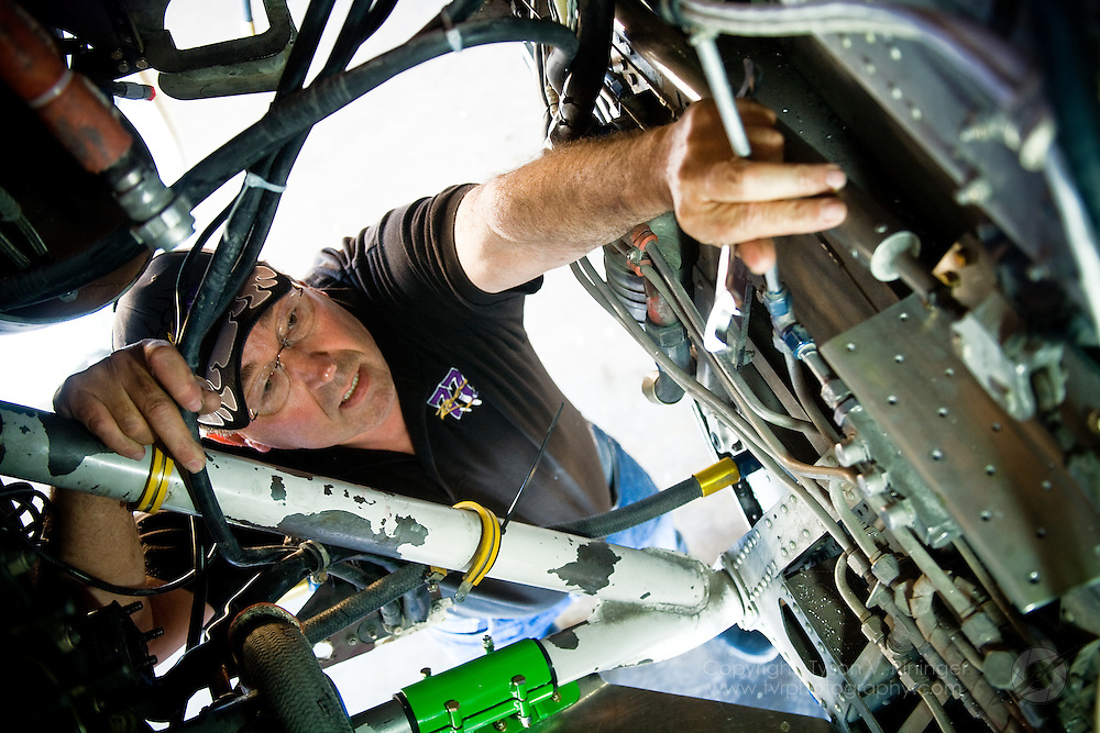 Crew Chief for the 2009 Rare Bear team, Dave Cornell, discusses improvements made to the highly modified F8f Bearcat prior to the Reno Air Racing Championship held at Stead Field near Reno, NV. Here he inspects the firewall just aft the engine.