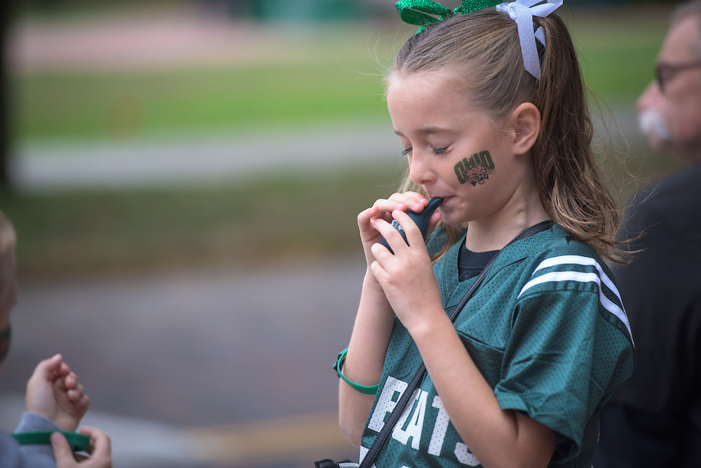Gabby Elliott blows up a balloon during a ribbon-cutting ceremony for Ohio University's College Gateway on October 8, 2016.