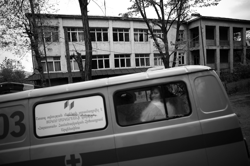 "A paramedics van arrives filled up with hospital staff. Hospital in Background. This image is part of the photoproject ""The Twentieth Spring"", a portrait of caucasian town Shushi 20 years after its so called ""Liberation"" by armenian fighters. In its more than two centuries old history Shushi was ruled by different powers like armeniens, persians, russian or aseris. In 1991 a fierce battle for Karabakhs independence from Azerbaijan began. During the breakdown of Sowjet Union armenians didn´t want to stay within the Republic of Azerbaijan anymore. 1992 armenians manage to takeover ""ancient armenian Shushi"" and pushed out remained aseris forces which had operate a rocket base there. Since then Shushi became an ""armenian town"" again. Today, 20 yeras after statement of Karabakhs independence Shushi tries to find it´s opportunities for it´s future. The less populated town is still affected by devastation and ruins by it´s violent history. Life is mostly a daily struggle for the inhabitants to get expenses covered, caused by a lack of jobs and almost no perspective for a sustainable economic development. Shushi depends on donations by diaspora armenians. On the other hand those donations have made it possible to rebuild a cultural centre, recover new asphalt roads and other infrastructure. 20 years after Shushis fall into armenian hands Babies get born and people won´t never be under aseris rule again. The bloody early 1990´s civil war has moved into the trenches of the frontline 20 kilometer away from Shushi where it stuck since 1994. The karabakh conflict is still not solved and could turn to an open war every day. Nonetheless life goes on on the south caucasian rocky tip above mountainious region of Karabakh where Shushi enthrones ever since centuries."