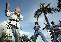 Karate coach Vicente Gonzalez, left, during his training session with his students John Paulo, 10, center, and Alejandro Casuso, 9, at Sunset Lake Community Center on Monday July 6, 2009. Staff photo/Cristobal Herrera..