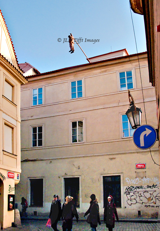Prague, soft sculpture of a hooded man hanging from a roof.  Four pedestrians (young women) walk underneath it, ignoring it.  Traffic sign: right turn arrow.  Graffiti on the wall of the three-storey building from which the figure hangs.