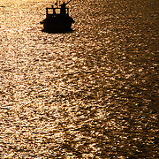 A single small fishing boat is silhouetted against the reflection on the water of the golden setting sun on the Bosporus (Bosphorus) Strait in Istanbul, Turkey.