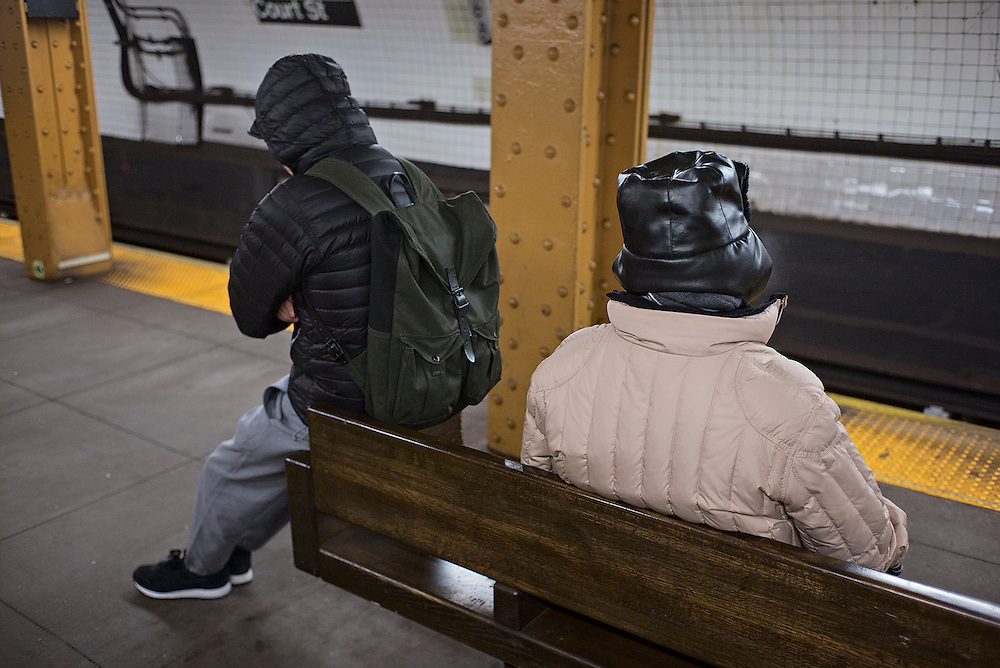 People bundled up against the cold while waiting for subway train, Brooklyn, NY, US