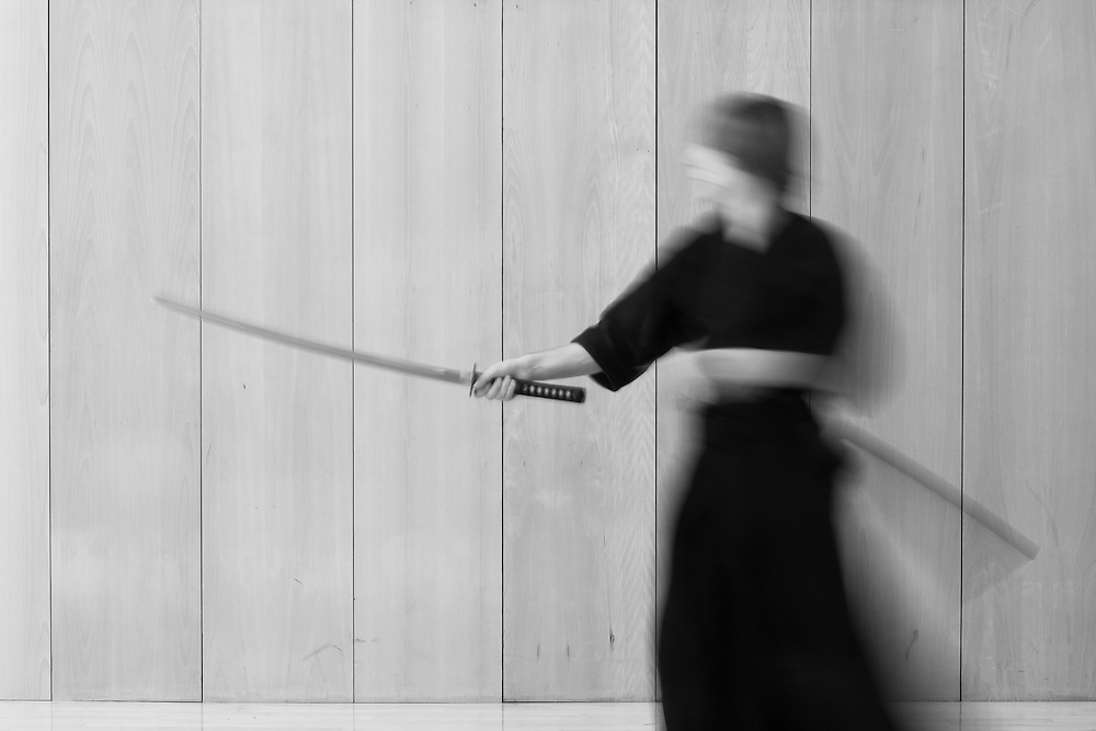 A iaido practicioner moves in an almost ghostlike fashion to prepare for a thrust with the sword