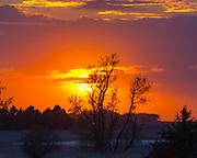 Orange sky haunts pond as the sun prepares to set.