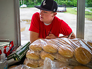 "26 JUNE 2020 - DES MOINES, IOWA: HUNTER (first name only) waits for a customer's order at Fair Food Friday in Des Moines. The 2020 Iowa State Fair, like many state fairs in the Midwest, has been cancelled this year because of the COVID-19 (Coronavirus) pandemic. The cancellation of the fair left many small vendors stranded with no income. Some of the fair food vendors in Iowa started ""Fair Food Fridays"" on a property a few miles south of the State Fairgrounds. People drive up and don't leave their cars while vendors bring them the usual midway fare; corndogs, fried tenderloin sandwiches, turkey legs, deep fried Oreos, lemonaide and smoothies. Fair Food Friday has been very successful. The vendors serve 450-500 people per Friday and during the lunch rush people wait in line in their cars 30 - 45 minutes to place an order.     PHOTO BY JACK KURTZ"