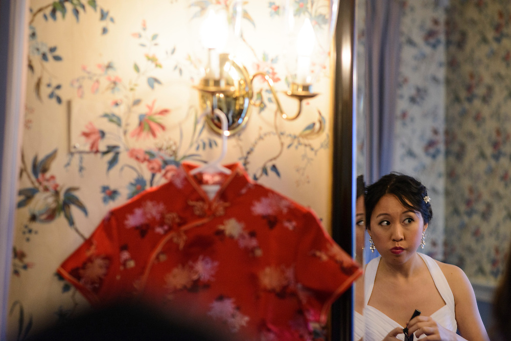 Photo by Matt Roth.Assignment ID: 30140754A..Evelyn Hsieh checks her lipstick in the Mount Vernon Inn sitting room before being introduced at her and her new husband Michael Wong's introduction at their reception at the the Mount Vernon Inn, in Mount Vernon, Virginia on Saturday, April 06, 2013.