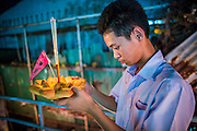 28 NOVEMBER 2012 - BANGKOK, THAILAND:  A boy in his school uniform prays before launching his krathong on Loy Krathong at Wat Yannawa in Bangkok. Loy Krathong takes place on the evening of the full moon of the 12th month in the traditional Thai lunar calendar. In the western calendar this usually falls in November. Loy means 'to float', while krathong refers to the usually lotus-shaped container which floats on the water. Traditional krathongs are made of the layers of the trunk of a banana tree or a spider lily plant. Now, many people use krathongs of baked bread which disintegrate in the water and feed the fish. A krathong is decorated with elaborately folded banana leaves, incense sticks, and a candle. A small coin is sometimes included as an offering to the river spirits. On the night of the full moon, Thais launch their krathong on a river, canal or a pond, making a wish as they do so.   PHOTO BY JACK KURTZ