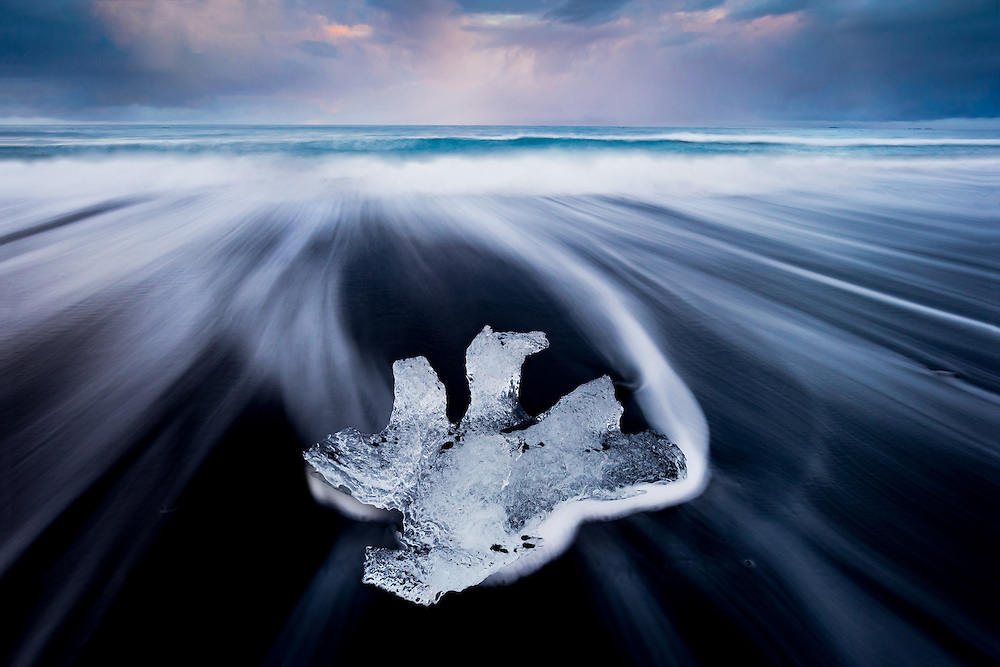 Small shapely iceberg on the black sand beach at Jökulsárlón in southern Iceland
