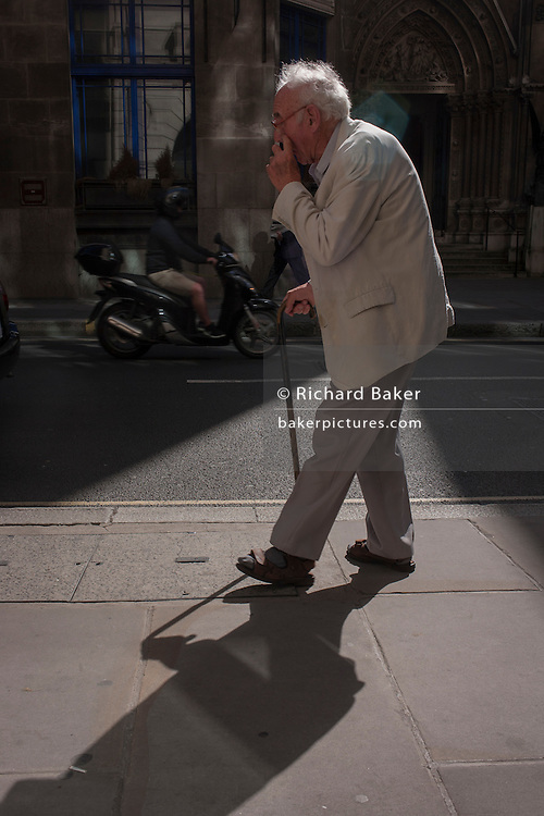 A frail, elderly man walks slowly with the help of a walking stick in sunlight, in the City of London, England UK.