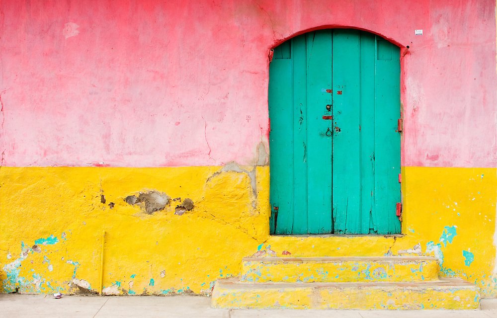 A wall and doorway, worn and chipped by the passing of time. This is a typical type of paint used on the colonial architecture of Granada, Nicaragua