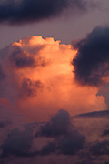 The setting sun lights up a cloud in the sky.