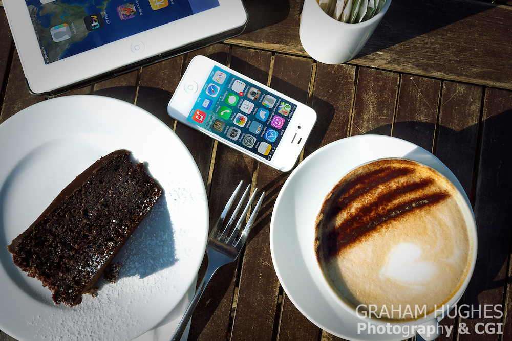 iPhone 4s, iPad 2 And Cake And Cappuccino On Table In Sunlight