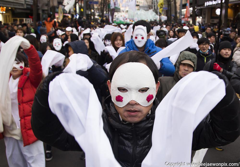 "Wearing masks, people march during an anti-government rally in Seoul, South Korea, December 5, 2015. The ""People's Camp for Rising Up and Fighting"", representing various groups of farmers, students, workers and the poor, demonstrated to oppose South Korean President Park Geun-hye to change the labor market which protesters insist, will allow easier layoff and more temporary workers and to monopolize the authorship of history textbooks. People wore masks at the rally to denounce Park who recently compared local protestors in masks to ISIS. The organizer said 50,000 people participated in the demo, while the police estimated that 14,000 attended. Photo by Lee Jae-Won (SOUTH KOREA)  www.leejaewonpix.com"