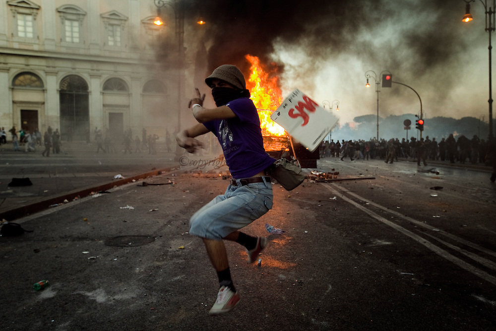ITALY, Rome, October 15, 2011 : A man jumps by a Police van in fire during a demonstration in Rome on October 15, 2011.© Christian Minelli.
