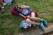 A tired long-distance runner wearing a kilt rests after finishing the London Marathon, in St James's Park, on 22nd April 2018, in London, England.