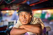 09 OCTOBER 2012 - BANGKOK, THAILAND:  A tuk-tuk driver in his tuk-tuk at the Bangkok Flower Market. A tuk-tuk is a three wheeled taxi common in Asia. The Bangkok Flower Market (Pak Klong Talad) is the biggest wholesale and retail fresh flower market in Bangkok. It is also one of the largest fresh fruit and produce markets in the city. The market is located in the old part of the city, south of Wat Po (Temple of the Reclining Buddha) and the Grand Palace.    PHOTO BY JACK KURTZ