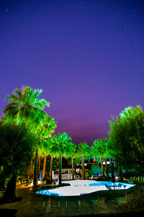 Night shot of pool and palm trees in Palm Springs, California. The sky is full of stars with pink and blue colors at the bottom.