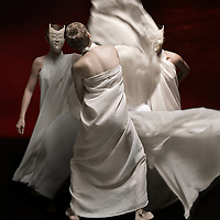 Dancers in flowing gowns perform under dramatic lighting amid a black backdrop