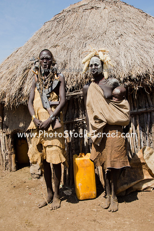 Mursi couple. The woman has an elongated lower lip to hold a clay disk as body ornamentstribe Debub Omo Zone, Ethiopia. Close to the Sudanese border.