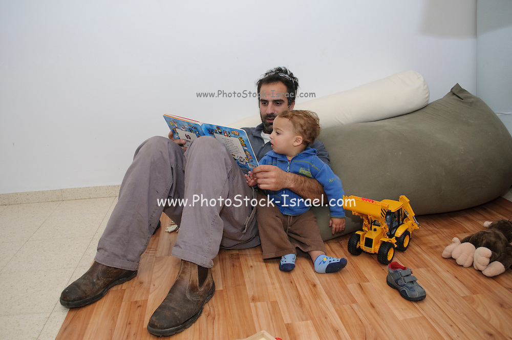 Father reading to his two year baby boy