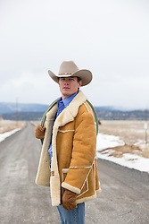 All American cowboy in Winter with a saddle