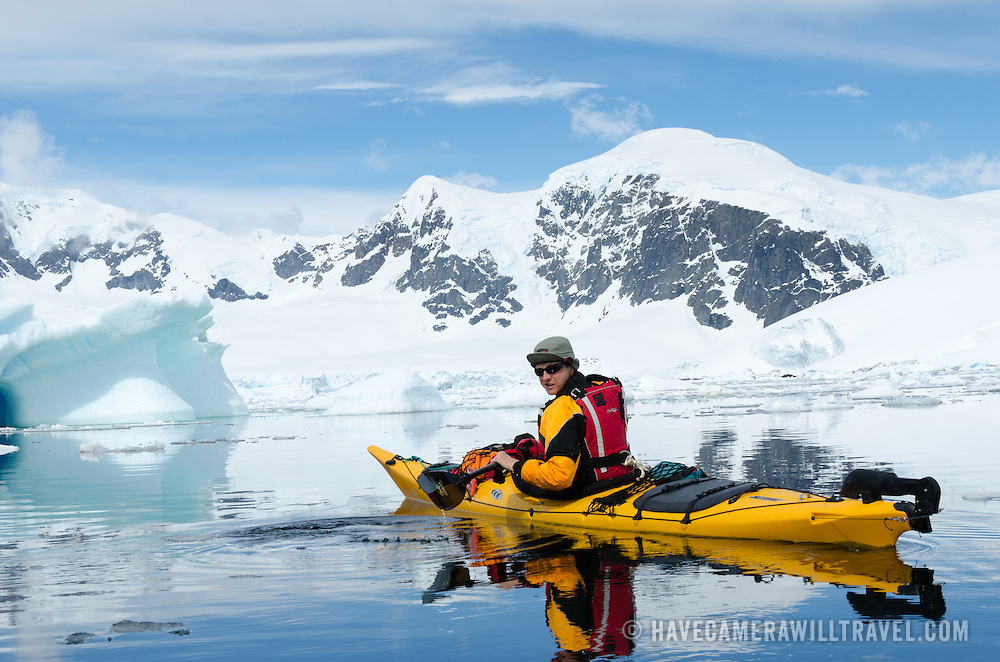 A solo kayaker on glassy still waters at Cuverville Island on the Antarctic Peninsula, with large snow-covered mountains in the background.