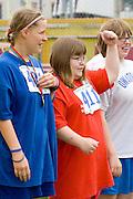 Three teen women Olympians on the award stand. Special Olympics U of M Bierman Athletic Complex. Minneapolis Minnesota USA