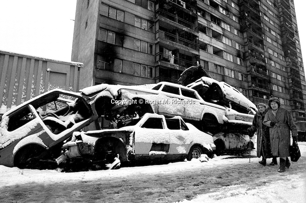 Elderly women walk past destroyed cars stacked to obscure the vision of Serb snipers during the final days of the siege of the city, Sarajevo, Bosnia and Herzegovina, February 1996. PHOTO BY ROGER RICHARDS